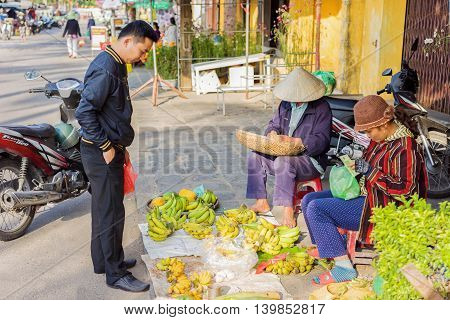 Asian Woman And Man Selling Bunches Of Bananas