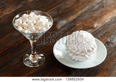 Glass With White Fluffy Marshmallows And Zephyr, Wooden Background
