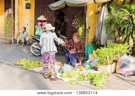Asian Woman Selling Bunches Of Bananas In The Street Market