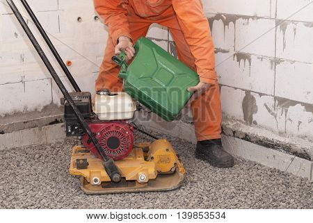 worker fills petrol into the tank plate compactors