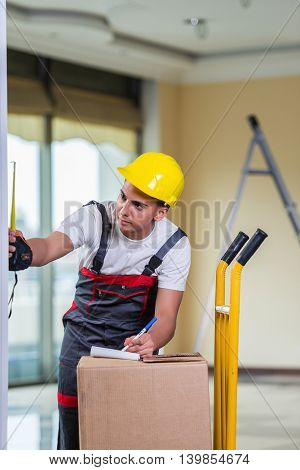 Delivery man taking dimensions with tape measure