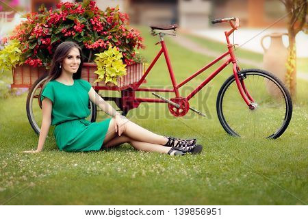 Woman Sitting on Grass Next to a Bike with Flowers