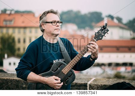 Prague, Czech Republic - October 10, 2014: Street Busker performing jazz songs at the Charles Bridge in Prague. Busking is legal form of earning money on Prague Streets.