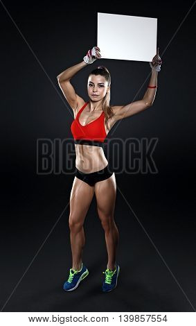 Young fitness female holding a blank sign over dark background, isolated with clipping path