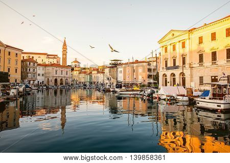 View on Piran medieval town from the bay with boats at the sunset in Slovenia