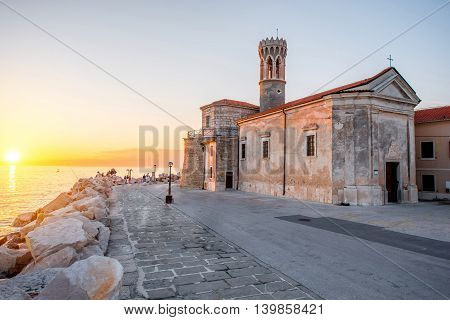Madona cape with saint Clement church in Piran town at the sunset in Slovenia