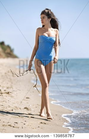 Barefoot model in the blue swimsuit walks on the beach on the background of the sea and the sky. She holds a tree branch in the right hand. Her head is partially turned to the right and she looks in front of herself with parted lips. Outdoors. Vertical.