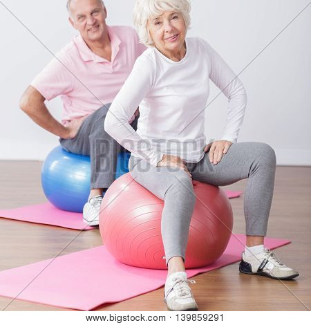 Photo of sporty elderly couple at gym having fun