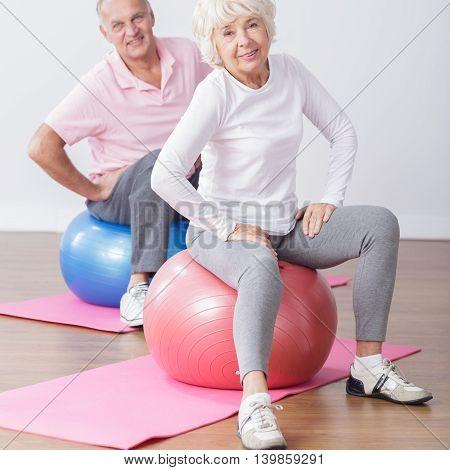 Photo of sporty elderly couple at gym having fun