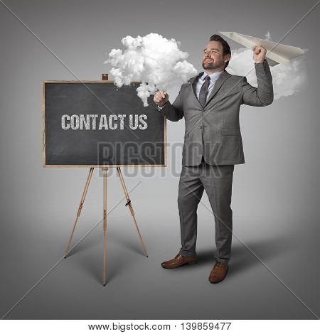 Contact Us text on blackboard with businessman and paper plane