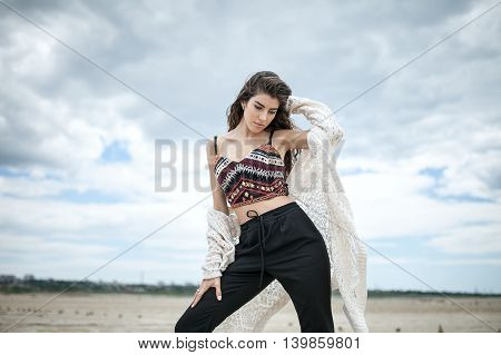 Thoughtful girl stands on the sand on the cloudy sky background. She wears black pants, multi-colored top with patterns and a white cardigan. Her right hand is on the right leg, left hand is on the hair. Outdoors. Horizontal.