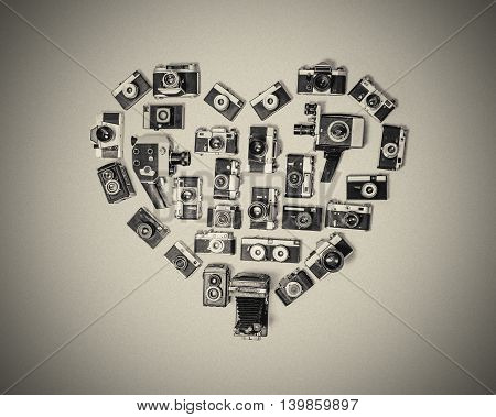 Black and white unusual image of heart assembled from retro cameras on a dark grainy background