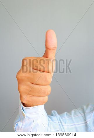Businessman hand showing thumbs up on gray background.