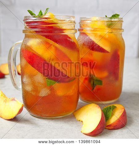 Mason jars of peach tea with ice