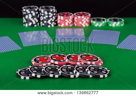 Green Casino Table With Covered Playing Cards, Red And Black Chips