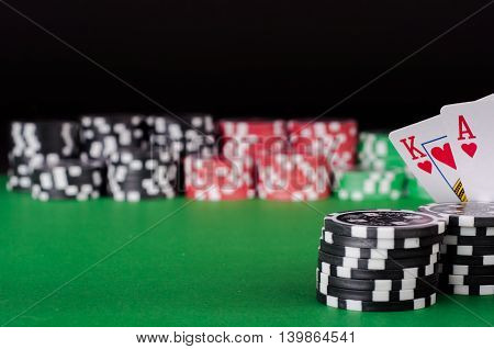 King, Ace, Black, Red And Green Casino Chips On Table