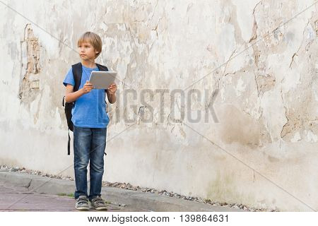 Child with tablet PC in the street. Boy holding computer iand looking around. Childhood education learning technology leisure concept