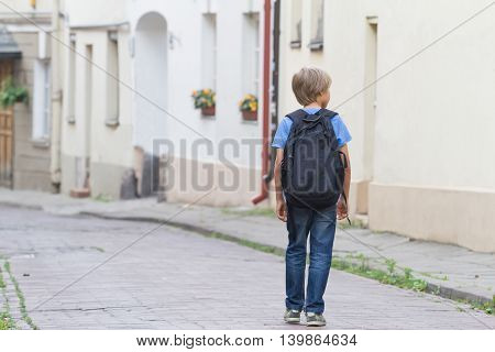 Little pretty schoolboy walking on the street with his backpack. Back view. People education back to school travel leisure concept