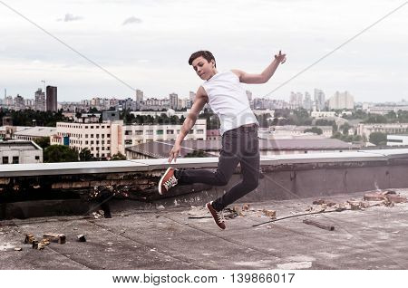 guy on the roof of a tall building jumps up