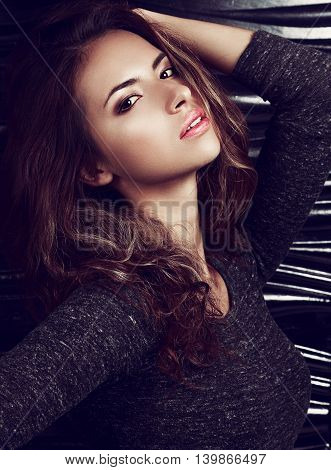 Sexy Makeup Hispanic Woman Posing On Black Wall Background With Long Curly Hair. Bright Closeup Fash