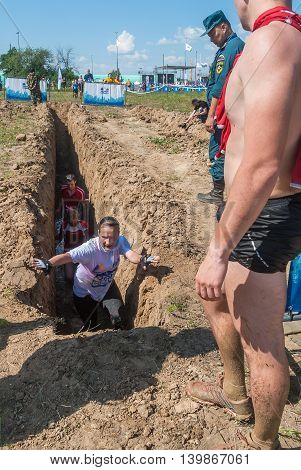 Tyumen, Russia - July 9, 2016: Steel Character extrim race on Voronino Hill. Running on a deep trench with water. Girl to get out to surface