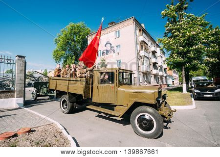 Gomel, Belarus  - May 9, 2016: Russian Soviet Military Truck ZIS-5V With Men On Board Dressed In Soldiers Uniform With Weapon Of WW2 Time, Victory Red Flag. Preparing For The 9th May Victory Parade.
