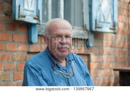 Outdoor portrait of elderly Ukrainian peasant sitting near his house