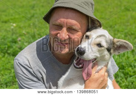 Outdoor portrait of two happy friends - mature man and his lovely young dog