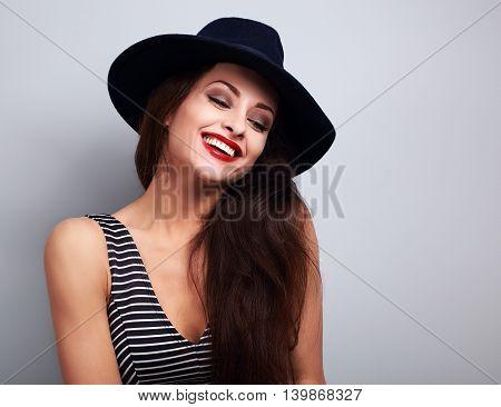 Happy makeup laughing female model in black elegant hat on blue background