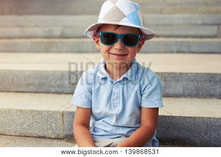 Close-up of little cute boy in sunglasses and hat sitting on concrete stairs on sunny day