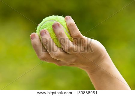 woman hand holding tennis ball on green blurred background