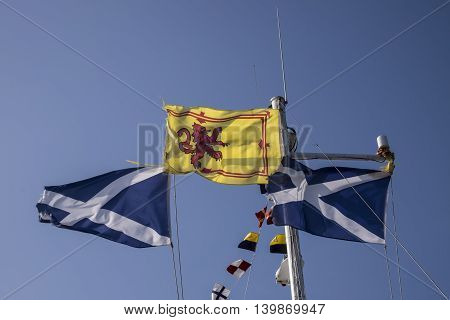 Royal Standard of Scotland with its red rampant lion on yellow background between two Scottish saltire flags with the cross of Saint Andrew of white and blue