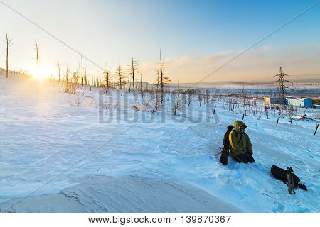 Photographer rests on the mountainside. Polar tundra winter.