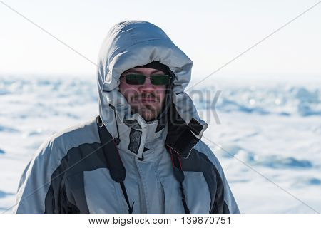 Portrait of a man in a gray down jacket. Sunny winter day in the Arctic tundra.