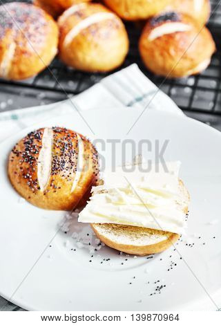 Homemade baked sliced pretzel bun with poppy seeds and butter on it on white plate. Group of many pretzel buns on back. This buns is german cuisine dish, ideal for lunch or breakfest with tea.