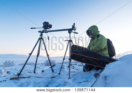 Man with photo camera on tripod taking timelapse photos in the arctic tundra. Poor lighting conditions.