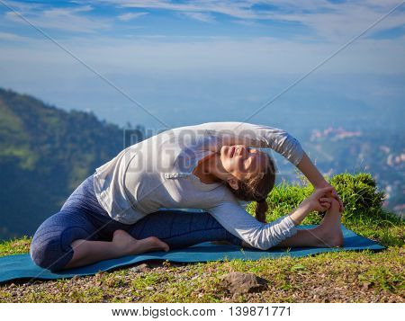 Yoga outdoors - young sporty fit woman doing Hatha Yoga asana parivritta janu sirsasana - Revolved Head-to-Knee Pose - in mountains in the morning