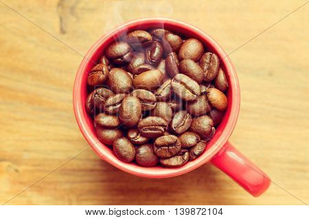 Coffee beans in red cup over wooden background