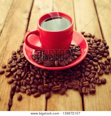 Red coffee cup with coffee beans on wooden background