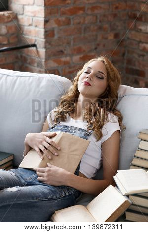 Education. Woman sitting on a sofa, surrounded with heap of books