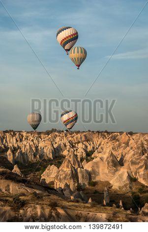 Balloons over valley in Cappadocia in the morning. Vertical shot.