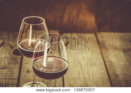 Glasses with red wine on rustic wood background, copy space