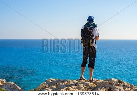 Hiker with a backpack standing on a rocky beach on the background of the vast sea. Back view. Cyprus Cape Greco Cavo Greco.