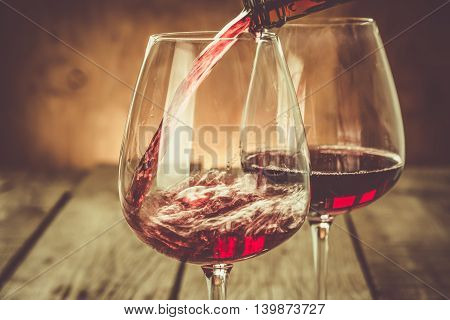 Pouring wine in a glass, copy space, toned