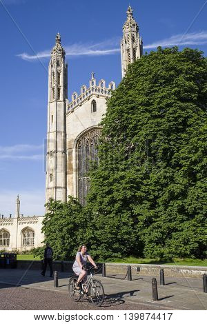 CAMBRIDGE UK - JULY 18TH 2016: A cyclist rides past the magnificent facade of Kings College Chapel in Cambridge on 18th July 2016.