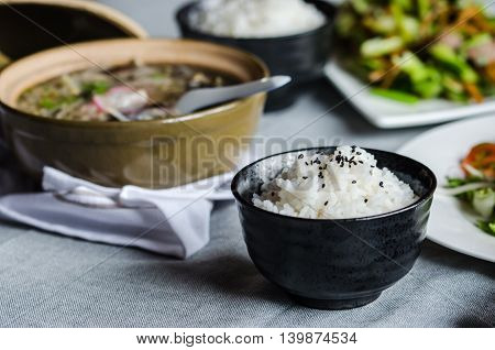 Bowl of rice with another asiatic foods at background
