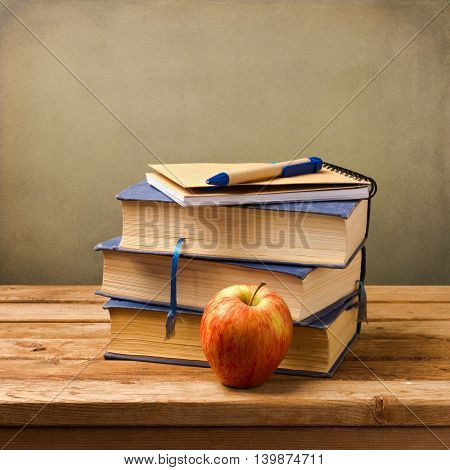 Stack of books with note book and apple. Back to school concept