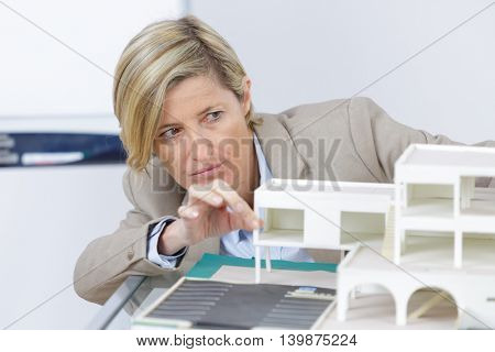 realtor woman reviewing scale model of houses