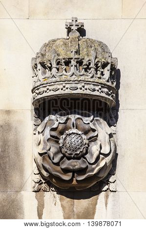 A carving of a Royal Crown and Tudor Rose on the exterior of the gatehouse at King's College in Cambridge UK.