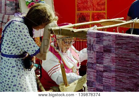 04.07.2015.Russia.Saint-Petersburg.Festival of the masters.A woman weaves a carpet as they did in the old days.